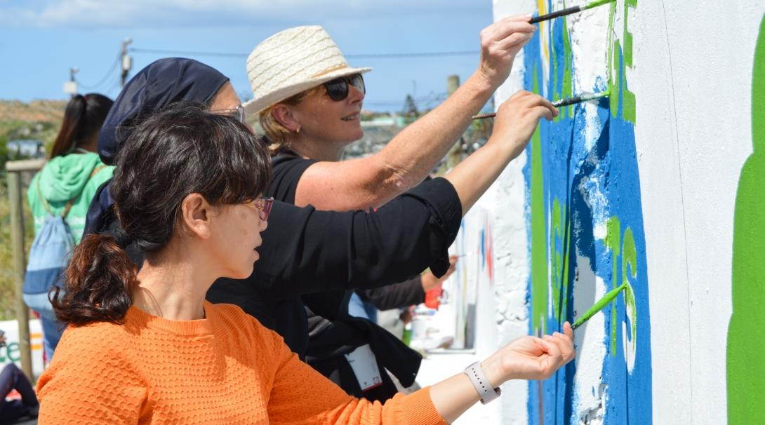 Volunteers work together to paint an educational mural while volunteering overseas on a project with no requirements.